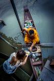 Munk Collecting Alms på den Amphawa floden fotografering för bildbyråer