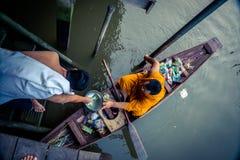 Munk Collecting Alms på den Amphawa floden arkivfoton