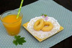 Munk på plattan och orange fruktsaft Arkivfoton