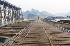 Munk som går på bambubron Arkivbild