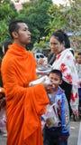 Munkar går passerandefolket som ger dem foods på Sangkhl Arkivfoton