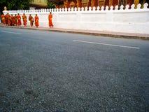 Munkar med bunkar bredvid tempelstaketet royaltyfri bild