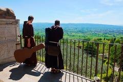 Munkar med gitarren i staden av Assisi royaltyfria bilder