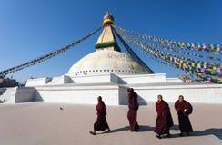 Munkar som går runt om den Boudhanath stupaen Arkivfoto