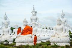 Munkar som klär en av den vita Buddhabilden med ämbetsdräkter Royaltyfria Bilder