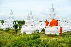 Munkar som klär en av den vita Buddhabilden med ämbetsdräkter Arkivfoto