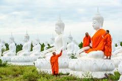 Munkar som klär en av den vita Buddhabilden med ämbetsdräkter Fotografering för Bildbyråer