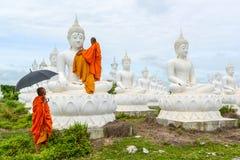 Munkar som klär en av den vita Buddhabilden med ämbetsdräkter Royaltyfria Foton