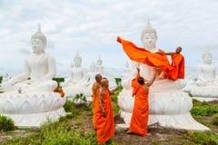 Munkar som klär en av den vita Buddhabilden med ämbetsdräkter Royaltyfri Fotografi