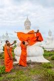 Munkar som klär en av den vita Buddhabilden med ämbetsdräkter Royaltyfri Bild
