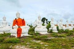 Munkar som klär en av den vita Buddhabilden med ämbetsdräkter Arkivfoton