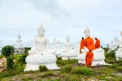 Munkar som klär en av den vita Buddhabilden med ämbetsdräkter Arkivbilder