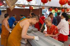 Munkar som skriver meddelanden på undersida av att taklägga Pannels på Wat Kh Royaltyfria Foton