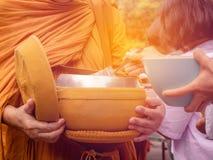 Munkarna av buddisten Sangha ger allmosa till en buddistisk munk, som kom ut ur de buddistiska offeringsna i morgonen _ arkivfoton