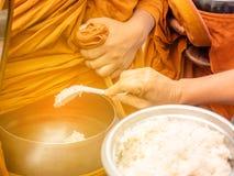 Munkarna av buddisten Sangha ger allmosa till en buddistisk munk, som kom ut ur de buddistiska offeringsna i morgonen _ royaltyfri foto