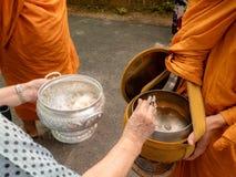 Munkarna av buddisten Sangha ger allmosa till en buddistisk munk, som kom ut ur de buddistiska offeringsna i morgonen _ royaltyfria bilder