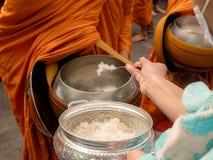 Munkarna av buddisten Sangha ger allmosa till en buddistisk munk, som kom ut ur de buddistiska offeringsna i morgonen _ arkivfoto