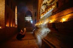 Munken ber med stearinljuset i Bagan, Myanmar Arkivfoto
