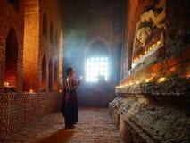 Munken ber med stearinljuset i Bagan, Myanmar Arkivbilder