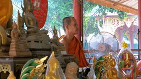 Munken knyter ett rep eller ett band till turisterna på den buddistiska templet av paradiset och helvete thailand arkivfilmer