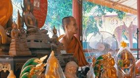 Munken knyter ett rep eller ett band till turisterna på den buddistiska templet av paradiset och helvete thailand stock video