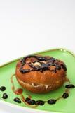 Munken med chokladpralin och jordgubben lagar mat med grädde på en platta royaltyfri bild