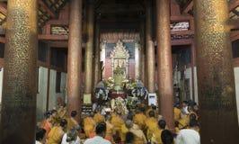 Munken och folket ber till den buddha reliken i buddistisk tempel Fotografering för Bildbyråer