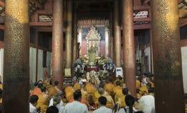 Munken och folket ber till den buddha reliken i buddistisk tempel Royaltyfria Bilder
