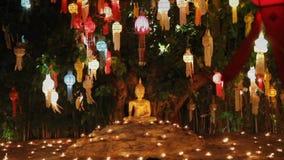 Munkljus per stearinljus till Buddha i templet, Chiang Mai, Thailand stock video