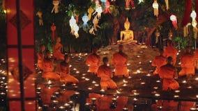 Munkljus per stearinljus till Buddha i templet, Chiang Mai, Thailand arkivfilmer