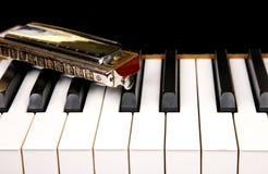 Munspel och piano Arkivbild