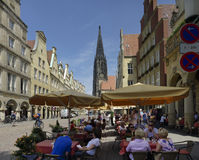 Munster, Germany. People on a terrace at the famous Prinzipalmarkt in Munster. Having been largely destroyed during World War II, the Prinzipalmarkt was Royalty Free Stock Images