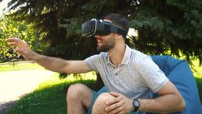 Munter grabb som undrar med virtuell verklighetexponeringsglas i påsestol utanför lager videofilmer
