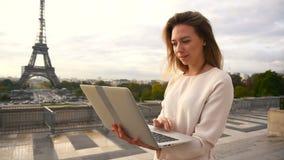 Munter kvinna som använder bärbara datorn med Eiffeltornbakgrund i ultrarapid stock video