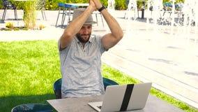 Munter manlig person som tycker om lyckad vad på bookmakerplats med bärbara datorn nära springbrunnen stock video