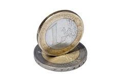 Muntstuk één euro op een ander euro muntstuk op wit Stock Fotografie