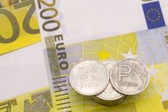 Muntstuk één roebel en de Europese munt: bankbiljetten van vijf vijftig euro muntstukken stock fotografie