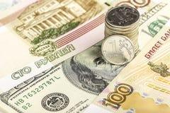 Muntstuk één roebel tegen de achtergrond van Russische en Amerikaanse bedelaars Stock Foto