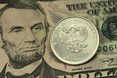 Muntstuk in één Russische roebel tegen de achtergrond van vijf Amerikaanse dollars Royalty-vrije Stock Foto's