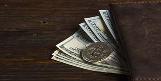 Muntstuk bitcoin tegen chaotically geschikte 100 dollarsrekeningen Royalty-vrije Stock Afbeeldingen