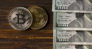 Muntstuk bitcoin tegen chaotically geschikte 100 dollarsrekeningen Stock Foto's