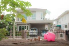 Muntstuk en spaarvarken op houten De besparing voor koopt huisconcept blur stock foto