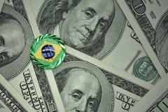 muntstuk met dollarteken met nationale vlag van Brazilië op de de bankbiljettenachtergrond van het dollargeld Stock Foto