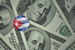 muntstuk met dollarteken met nationale vlag van Cuba op de de bankbiljettenachtergrond van het dollargeld Stock Foto
