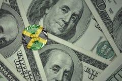 muntstuk met dollarteken met nationale vlag van Jamaïca op de de bankbiljettenachtergrond van het dollargeld Stock Foto
