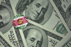 muntstuk met dollarteken met nationale vlag van suriname op de de bankbiljettenachtergrond van het dollargeld Stock Fotografie