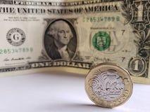 muntstuk van één echt pond en Amerikaanse dollarrekening