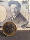 muntstuk van één euro en Japans bankbiljet van 1000 Yen royalty-vrije stock foto's
