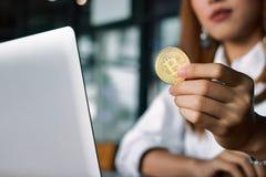 Muntstuk van Cryptocurrency wordt het gouden bitcoin gehouden op hand ` s van bedrijfsvrouw Virtueel geld op digitaal stock foto