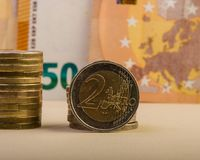 Muntstuk van twee euro en een stapel gevouwen muntstukken tegen een backgrou Stock Afbeeldingen